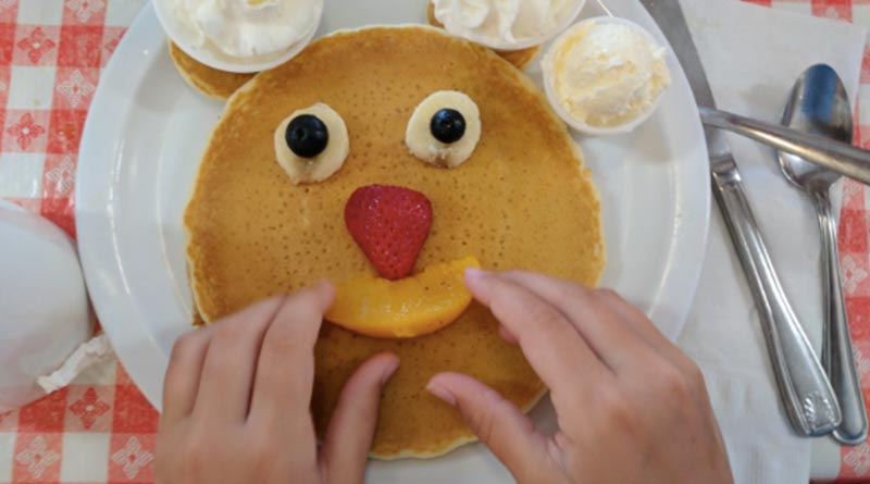 Iden Elliott adjusts a smiley face on pancakes at Ellen's Danish Pancake House in Buellton, Calif.