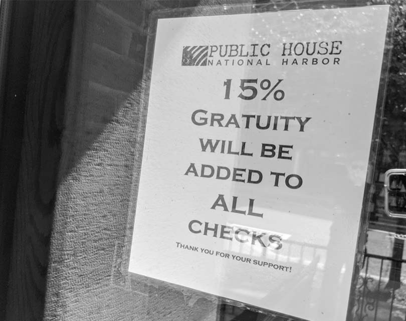 This sign warns customers of the required gratuity that they'll add to the final bill.