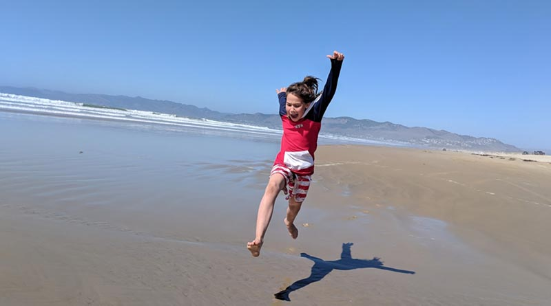 Erysse Elliott jumps over a puddle at Pismo Beach in Central California